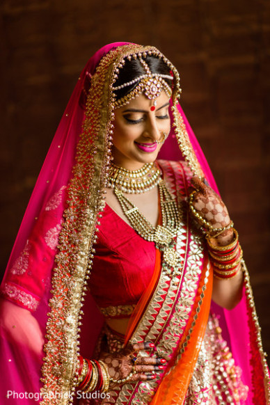 Lovely indian bride posing in her hot pink wedding attire ...