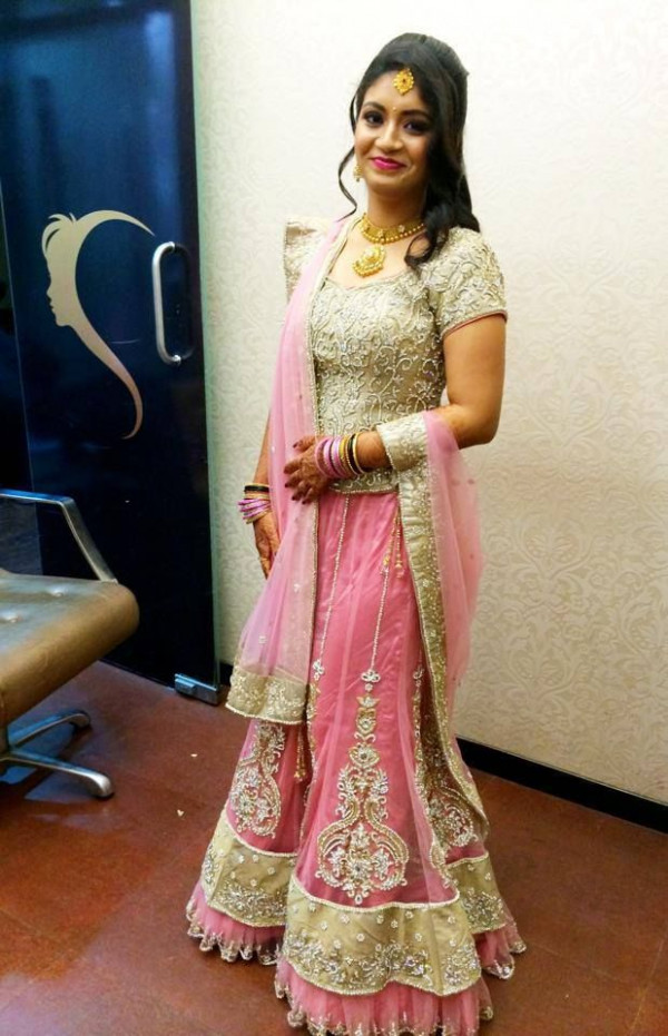 Traditional Indian bride wearing bridal hair, lehenga and ...